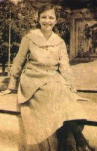 young woman sitting outside and smiling into the camera