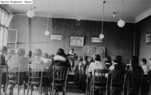 b&w photo of classroom with view of students backs and a teacher at the front of the room