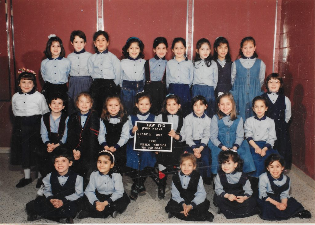 Three rows of girls, one standing on a bench, one sitting on a bench, and one sitting on the floor.  Two girls in the middle row hold a black-and-white sign identifying the class. The girls wear uniforms of light blue shirts with dark blue collars, and dark blue skirts or jumpers. Two girls wear denim jumpers.